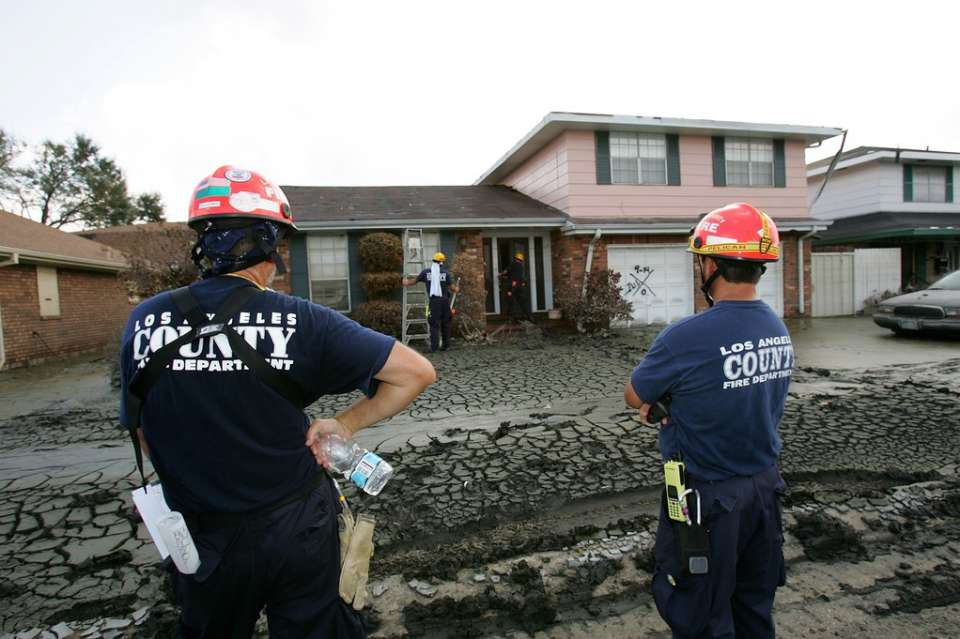 Chalmette, La., Sept. 17, 2005 -- John Haugh and Dan Gordon watch as members of their California Task Force 2's Urban Search and Rescue team go house to house looking for survivors from Hurricane Katrina. Bob McMillan/ FEMA Photo