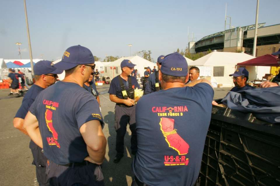 New Orleans, La., Sept. 15, 2005 -- Members of California Task Force 3 Urban Search and Rescue team are being briefed before heading out on a rescue mission. Bob McMillan/ FEMA Photo